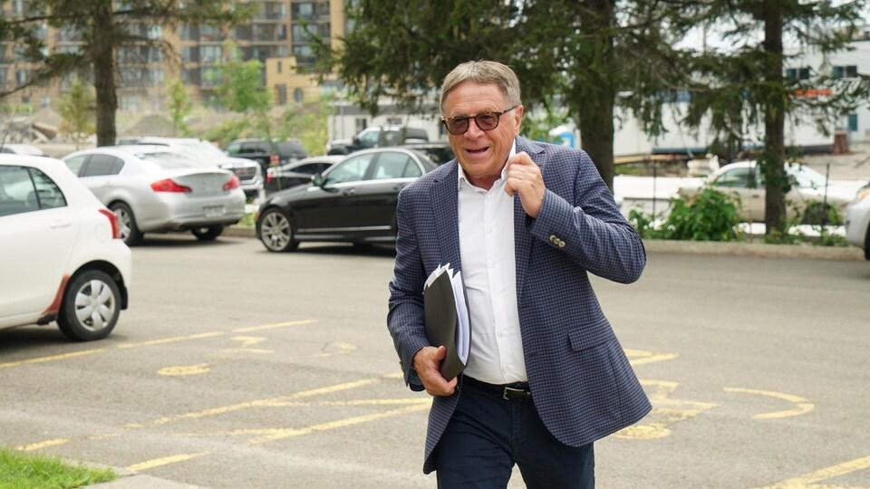 Gilles Lehouillier à son arrivée à la réunion du comité consultatif sur le troisième lien. Il porte des lunettes fumées, une chemise blanche, un veston à carreaux bleus et noirs ainsi qu'un pantalon bleu marine.