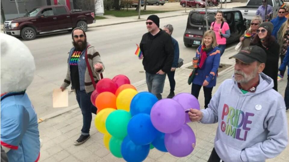Des gens dans la rue. On voit des ballons et des grapeaux aux couleurs de l'arc-en-ciel.