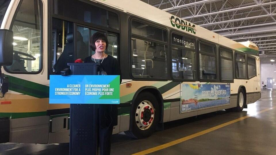 La ministre de la Santé Ginette Petitpas Taylor fait une annonce à la centrale des autobus municipaux Codiac à Moncton, devant un autobus.