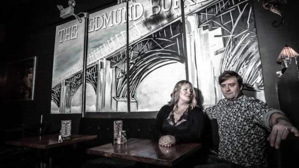Un couple assis à une table dans un bar vide.