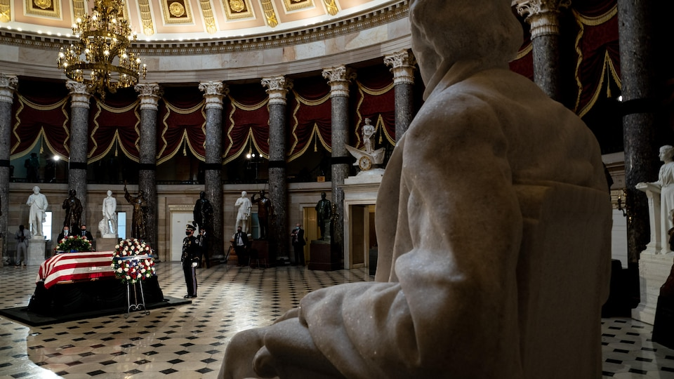 Le cercueil de Ruth Bader Ginsburg, au milieu d'une salle pleine de statues.