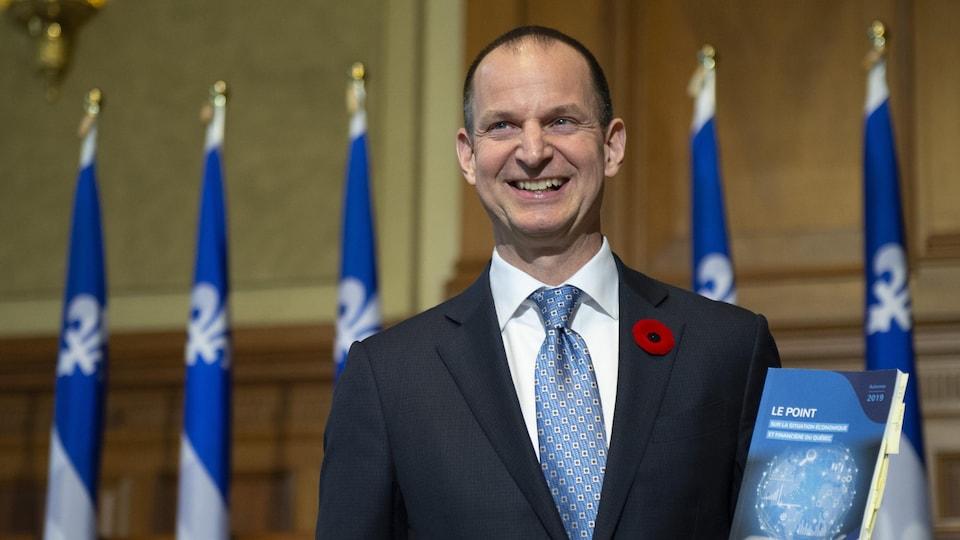 Eric Girard, souriant, tenant dans sa main gauche une copie de sa mise à jour économique.
