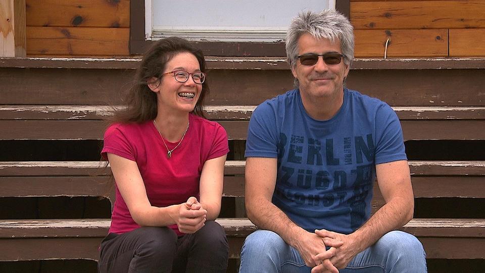 Émilie Leblanc-Laberge et Joël Lebreux sont assis dans les escaliers en bois de leur gîte.