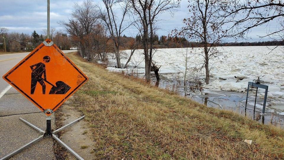Un panneau d'avertissement orange à côté d'une route bordée de près par une rivière glacée.