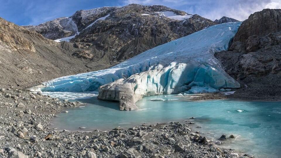 De la glace qui s'avance et fond dans un lac, sur des rochers.
