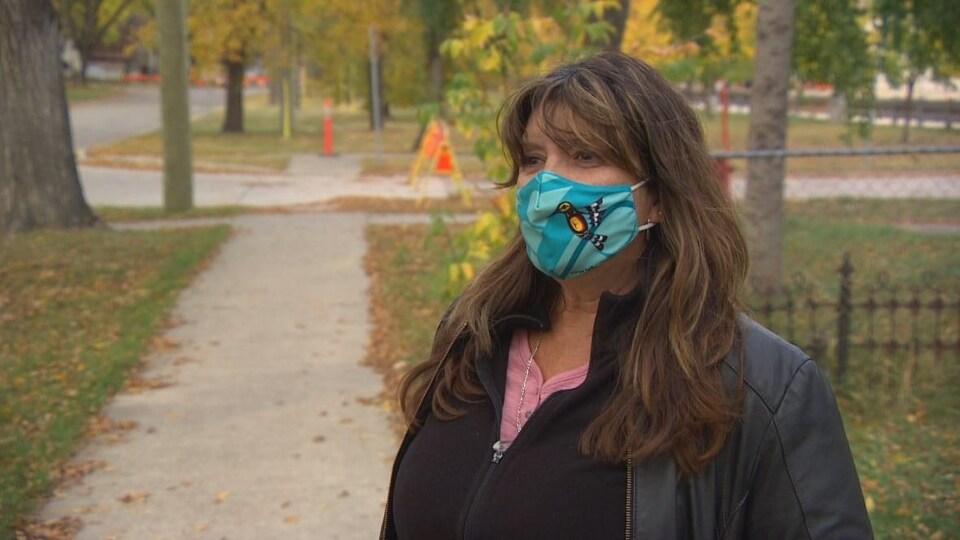 Une femme porte un couvre-visage et se tient debout sur un trottoir.