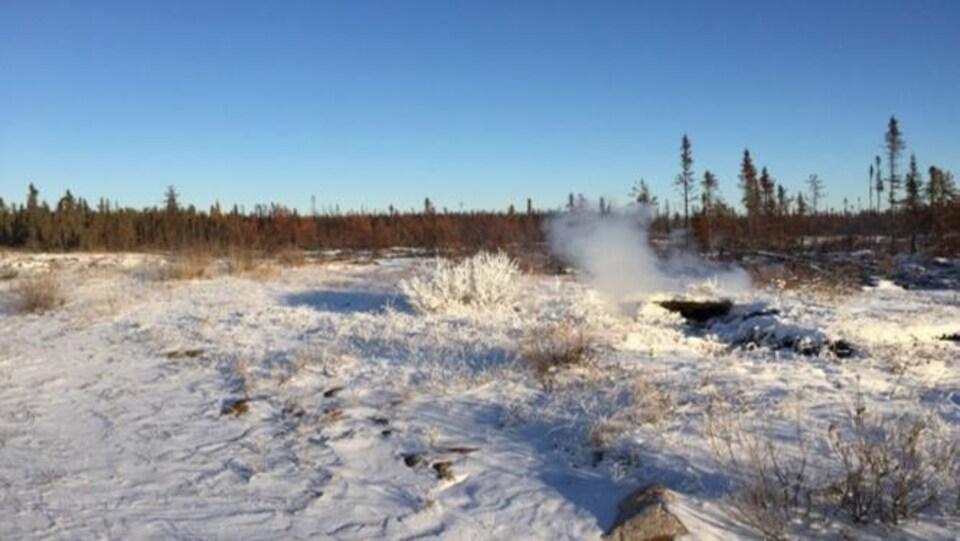 Un feu zombie fume dans une plaine près de Fort Smith, aux Territoires du Nord-Ouest, en décembre 2020.
