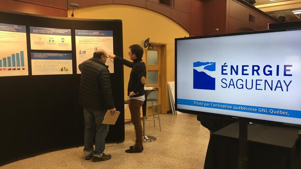 Une affiche d'Énergie Saguenay avec deux personnes en arrière-plan qui consultent des affiches.