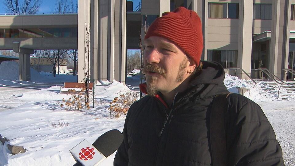 Un homme parle au micro à l'extérieur l'hiver.