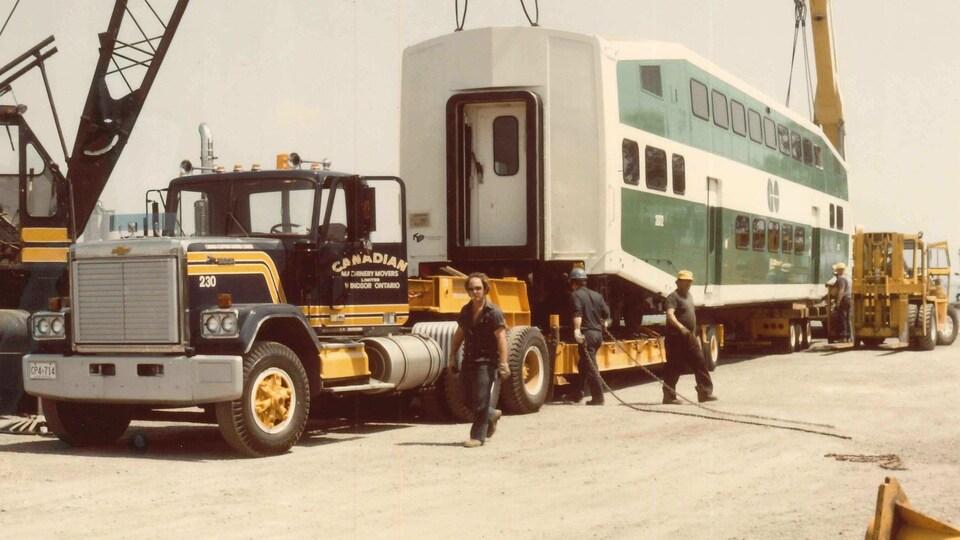 Une voiture de banlieue à deux étages transportée par camion.