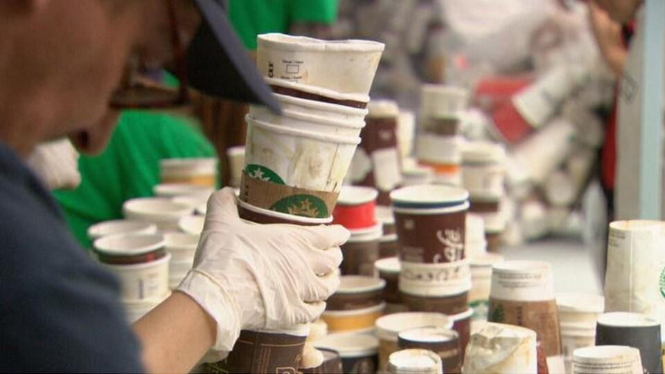 Une main gantée tient une pile de contenants en carton et on vous aussi plusieurs contenants similaires empilés en arrière-plan