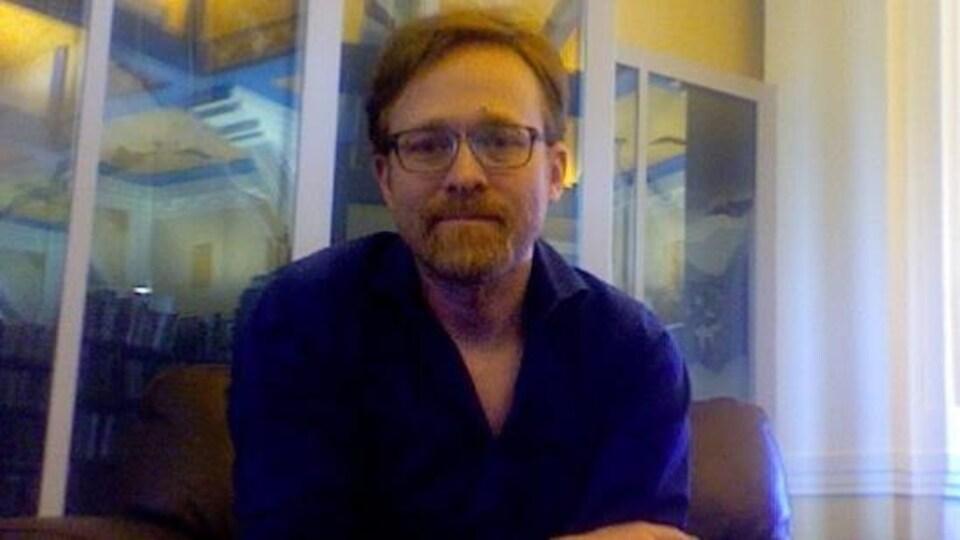 Un homme assis avec des lunettes et les bras croisés.