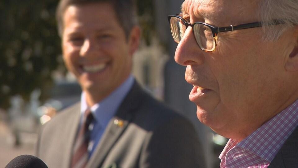 Sam Katz, en compagnie du maire Brian Bowman, parle au micro devant des journalistes.