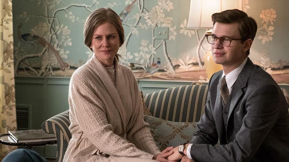 Une femme et un jeune homme assis sur un divan se tiennent la main.