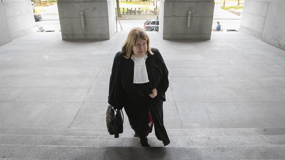 Une femme en toge gravit les escaliers extérieurs du palais de justice de Montréal.