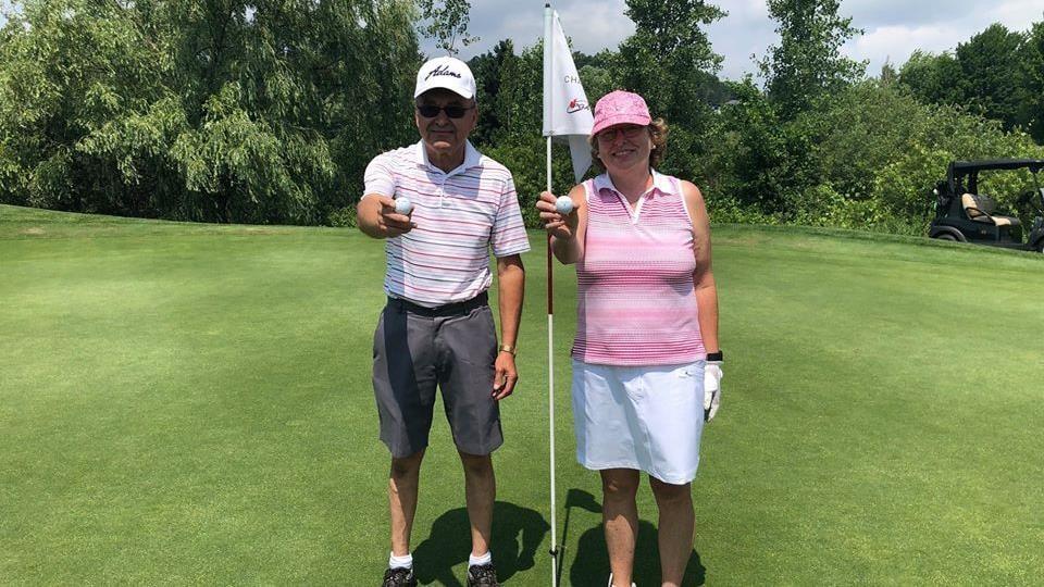 Denis L'Heureux et Linda Carreau au trou numéro 13 tenant fièrement leur balle dans leurs mains.
