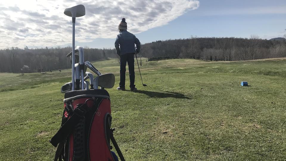 Un élève joue au golf, son sac au premier plan.