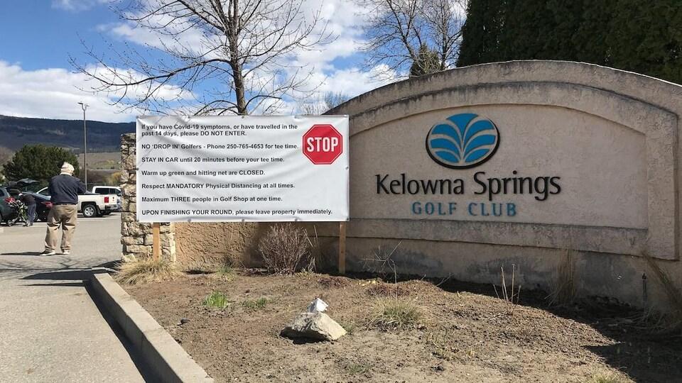 Une grande affiche énumère les règles de distanciation sociale à l'entrée du club de golf Kelowna Springs.