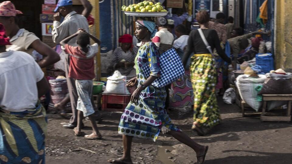Une vendeuse transportant un plateau de fruits sur sa tête marche dans une rue de Goma.