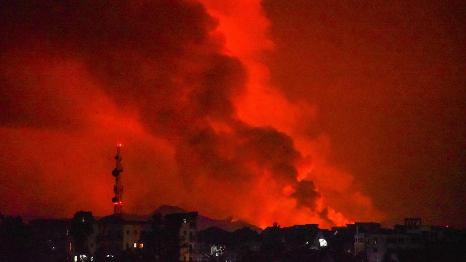 La nuit remplie de fumée et du feu sortant d'un volcan en éruption.