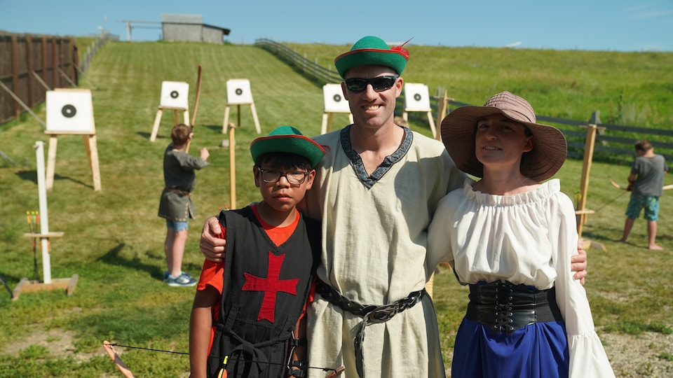 Une famille habillée comme au Moyen Âge devant des cibles de tirs à l'arc.