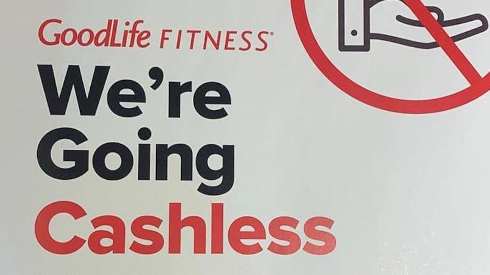 Une affiche qui indique qu'une succursale de GoodLife Fitness n'acceptera plus l'argent comptant.