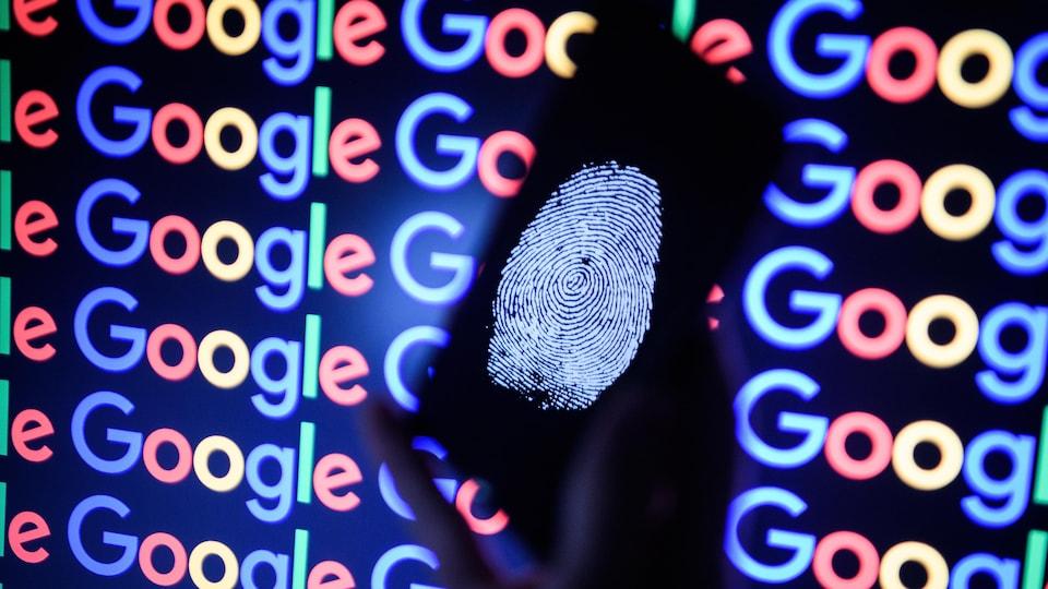 Une main tient un téléphone cellulaire qui affiche une empreinte digitale, devant plusieurs logos de Google.