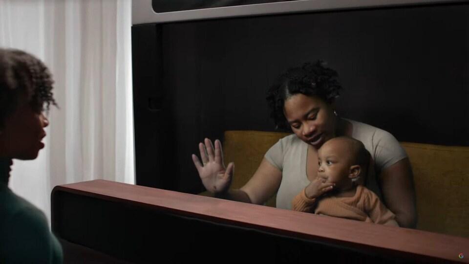 Une femme avec un bébé parle à une autre personne, mais une vitre les sépare.