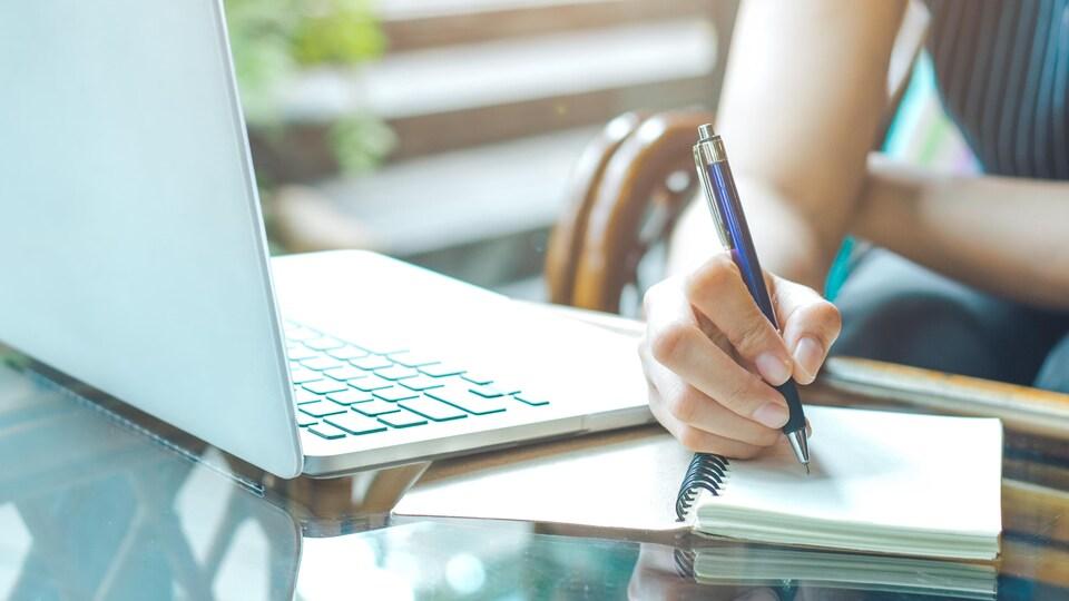 Une main de femme prend des notes dans un cahier, à côté d'un ordinateur portable.