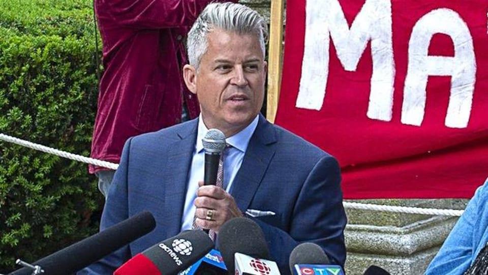 L'avocat Gordon Allen est assis et tient un micro lors d'une conférence de presse à l'extérieur.