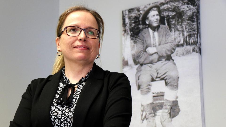 Une femme tient la même pause que celle prise par un monsieur en photo derrière elle en noir et blanc