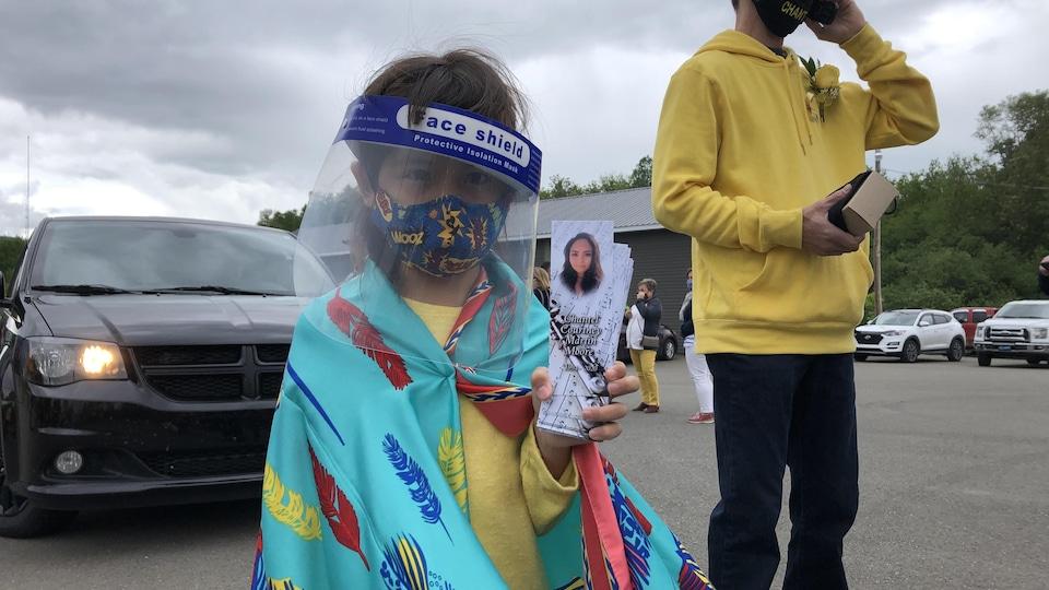 La petite Gracie, 6 ans, masquée, distribue des petits cartons à la mémoire de sa mère.