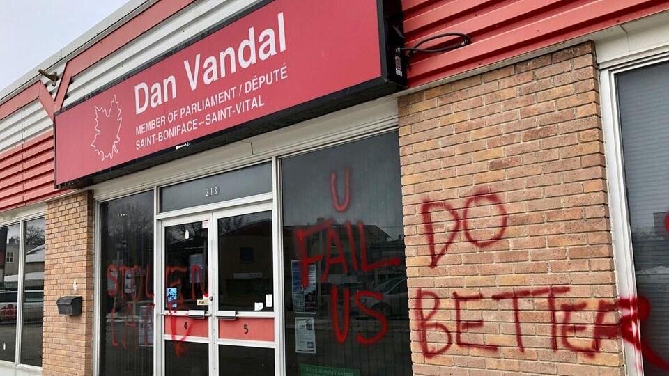 Des graffitis en anglais sur la devanture du bureau du député fédéral Daniel Vandal à Winnipeg.