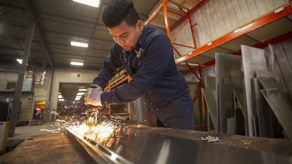 Un jeune homme manie un outil sur une surface en acier.