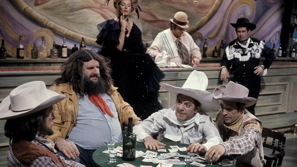 Dans un bar, des cowboys (le Grand Antonio, Olivier Guimond et Roger Michael) sont assis autour d'une table et jouent aux cartes pendant que la tenancière (Denise Pelletier), le barman (Rod Tremblay) et un cowboy (Denis Drouin) les observent au comptoir en arrière-plan.