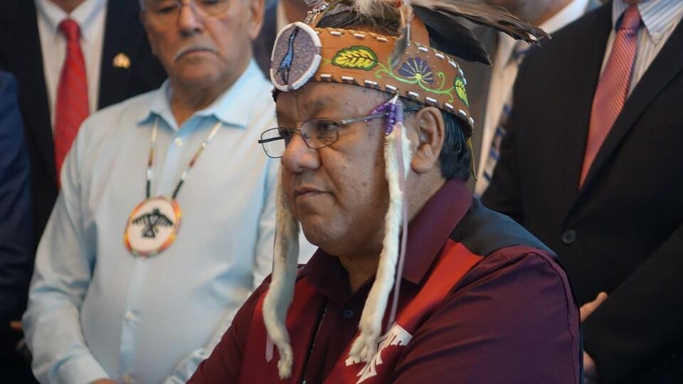 Un homme en costume autochtone traditionnel est entouré de personnes.