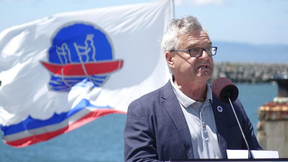 Le grand chef Jacques Tremblay devant un drapeau de la nation Wolastoqiyik Wahsipekuk.