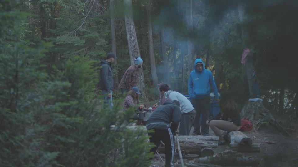 Des adolescents en forêt cuisinent autour d'un feu de camp.