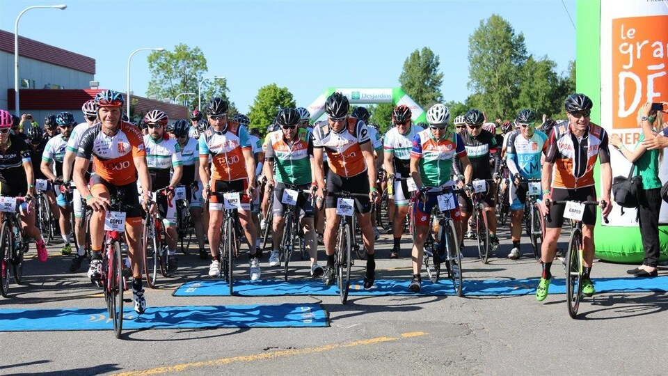 Des cyclistes sont regroupés à la ligne de départ et attendent le signal pour partir