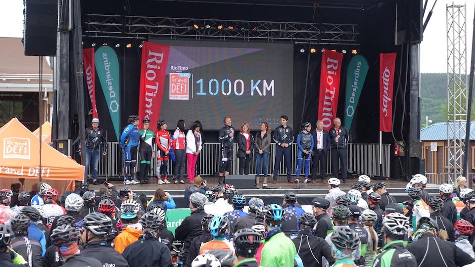 Des personnes se trouvent sur une scène. Des cyclistes se trouvent dans la foule.