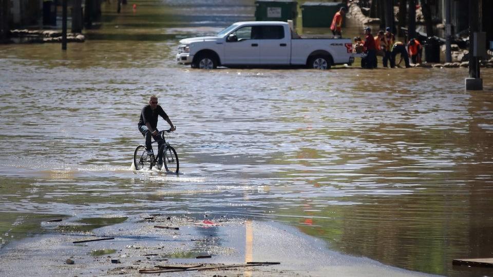 Un homme conduit son vélo dans les eaux au centre-ville de Grand Forks alors que des travailleurs installent des sacs de sable en arrière plan.