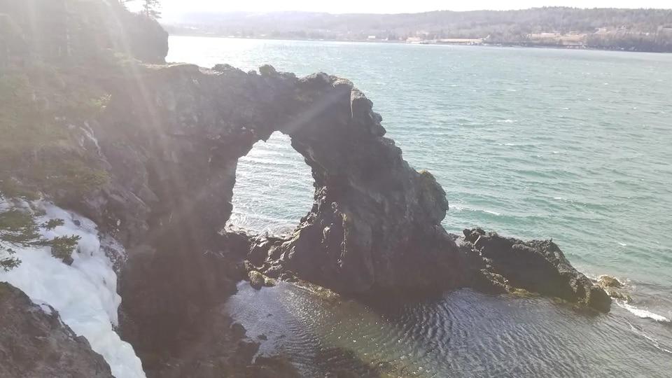 Un rocher percé par l'érosion le long d'une falaise