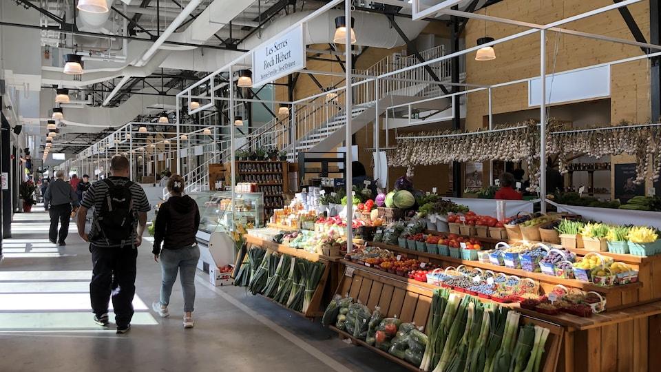 Des gens marchent devant des kiosques de fruits et de légumes.