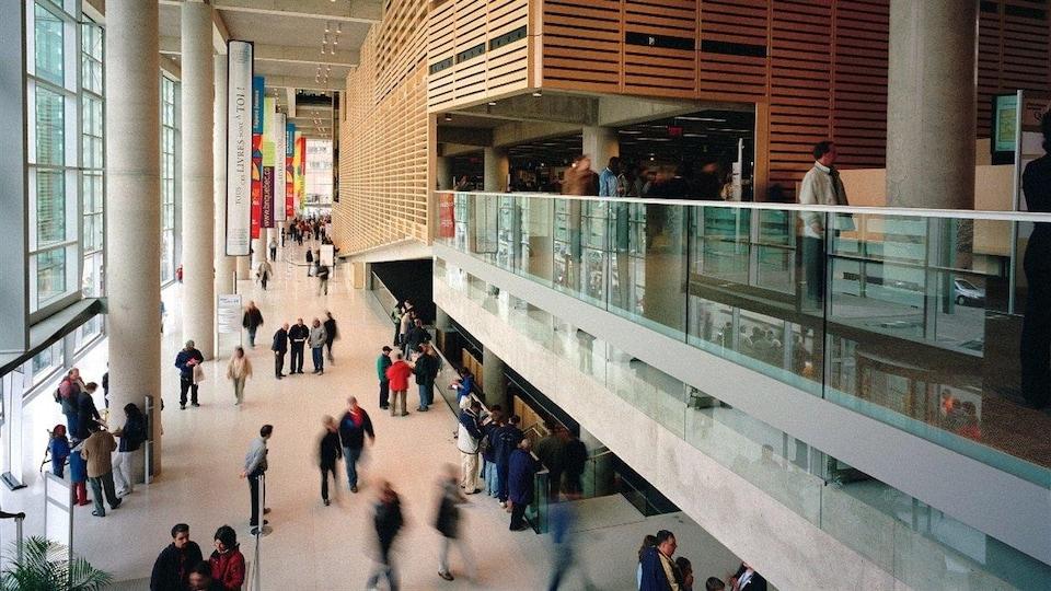 Des gens marchent dans les corridors d'un bâtiment.