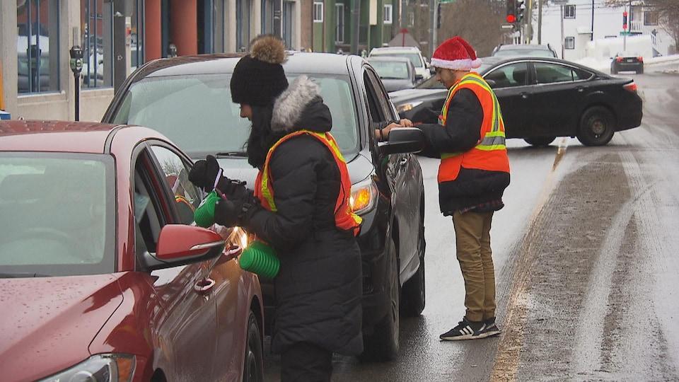 Gens qui récoltent les dons d'automobilistes dans la rue.