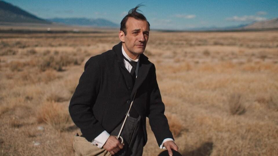 Un homme marche seul au milieu d'un paysage désertique.