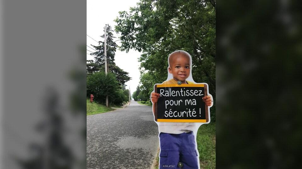 Petit enfant qui tient un tableau disant : Ralentissez pour ma sécurité ! sur le bord de la route.
