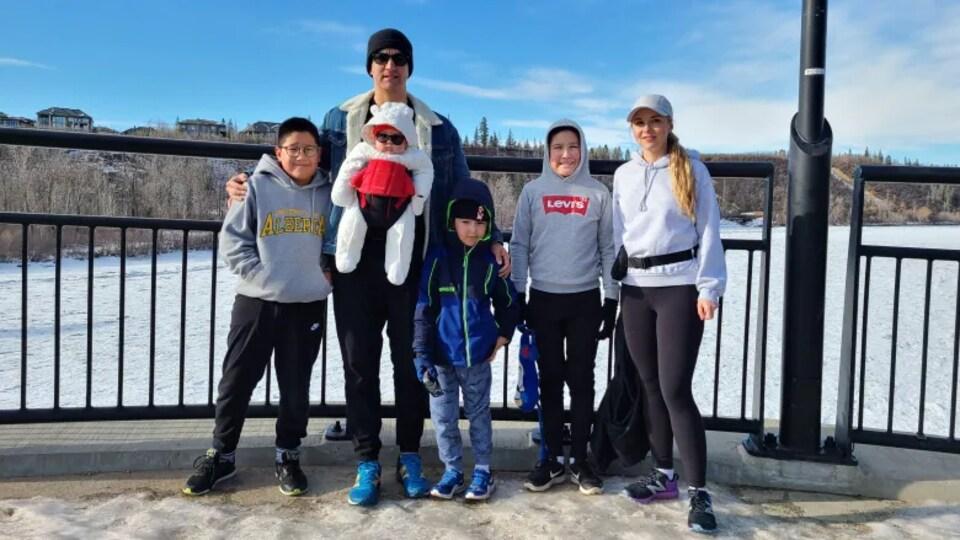 Dans une scène d'hiver, Grant Bruno, ses quatre enfants et sa partenaire sourient.