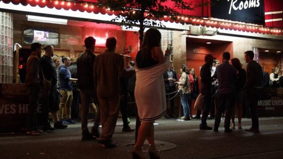 Des passants déambulent devant un bar de la rue Granville à Vancouver.