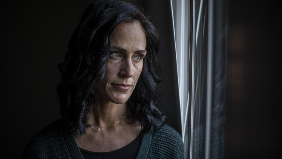 Une femme aux cheveux noirs regarde par la fenêtre.